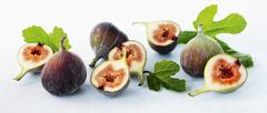 Fresh figs with leaves, whole and halves - stock photo