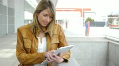 woman using electronic tablet in front of modern building - stock footage