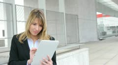 Businesswoman using electronic tablet outside the office Stock Footage