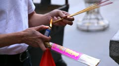 Man lighting the incense before praying in temple daylight Stock Footage