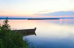 sunset with boat near the summer lake shore - stock photo