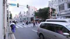 People cross intersection while policeman supervise - stock footage