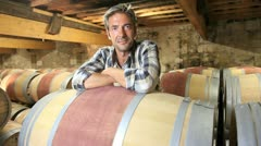 smiling winemaker leaning on wine barrel in winery - stock footage