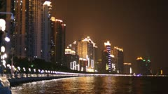 Building with neon lights reflecting in the river at night Stock Footage