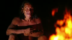 Huaorani hunter resting by the fire, Yasuni Huaorani reserve, Ecuador Noisy due - stock footage