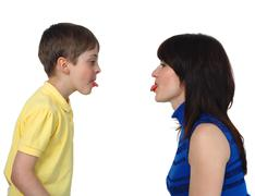 Boy and woman put out each other tongues Stock Photos