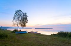 sunset with boats near the summer lake shore - stock photo
