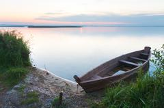 sunset with old flooding boat on summer lake shore - stock photo