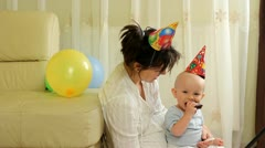 Mom and baby with colorful crests celebrating birthday - stock footage