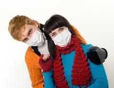 man embraces a woman wearing masks, flu, - stock photo