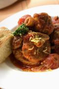 Osso buco with tomatoes and focaccia - stock photo