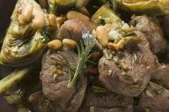 Lamb with artichokes, herbs and pine nuts Stock Photos
