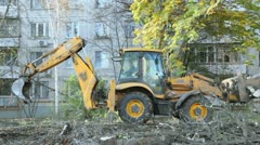 Excavator closes jib near dwelling house at autumn day Stock Footage