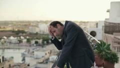 Young tired, frustrated businessman resting on terrace, crane shot HD Stock Footage