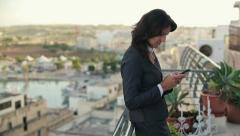 Young businesswoman using smartphone on terrace, crane shot HD Stock Footage