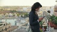 Stock Video Footage of Young businesswoman using smartphone on terrace, crane shot HD