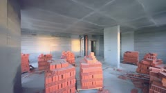 Bricks inside unfinished room lit by sun light from windows Stock Footage