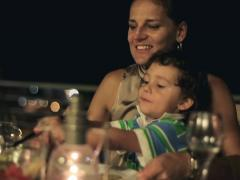 Happy family eating dinner in the evening, steadicam shot NTSC Stock Footage