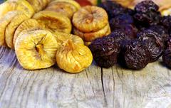 dried plums and figs in wooden table - stock photo