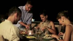 Friends eating dinner in the evening, steadicam shot HD Stock Footage
