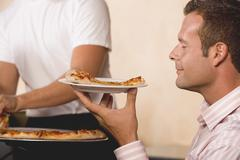 Man with contented expression holding slice of pizza on plate Stock Photos
