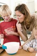 Mother and son tasting baking mixture - stock photo