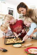 Mother and children making piped biscuits Stock Photos