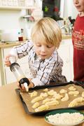 Boy piping biscuit dough onto baking tray with biscuit syringe - stock photo