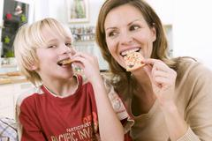 Mother and son eating Christmas biscuits - stock photo