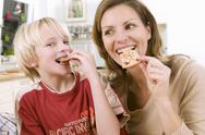 Mother and son eating Christmas biscuits Stock Photos