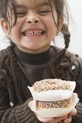 Giggling girl holding two doughnuts with sprinkles - stock photo