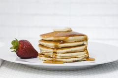 Stock Photo of Pancakes with maple syrup, butter and a strawberry