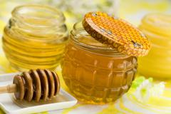 Jars of honey and honey dipper Stock Photos