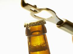 Beer bottle neck with crown cap and bottle opener Stock Photos