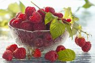 Stock Photo of Fresh raspberries with leaves in a bowl