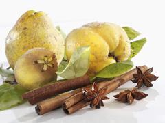 Quinces, cinnamon sticks and star anise Stock Photos
