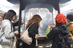 inhaling incense smoke in tokyo - stock photo