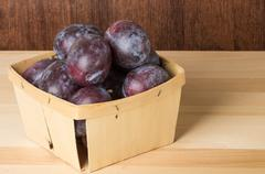 Container of prune plums on table Stock Photos