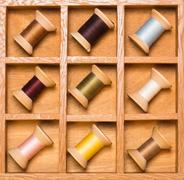 wooden shadow box with wooden thread spools - stock photo