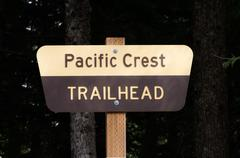 pacific crest trail sign on post with dark background - stock photo