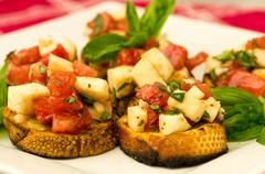 fresh bruschetta with tomatoes mozzarella cheese and basil on plate - stock photo