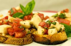 fresh bruschetta with tomatoes mozzarella cheese and basil - stock photo