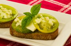 Stock Photo of fresh bruschetta with green heirloom tomatoes cheese and basil