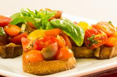 fresh bruschetta with mixed tomatoes cheese and basil on plate - stock photo