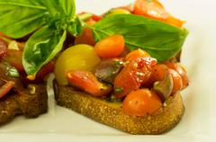 fresh bruschetta with mixed tomatoes cheese and basil - stock photo