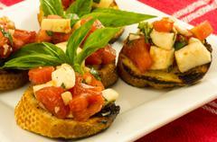Fresh bruschetta with tomatoes cheese basil on white plate Stock Photos