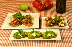 Fresh bruschetta with tomatoes cheese basil and wine bottle Stock Photos