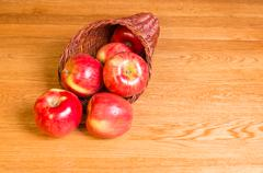 Red apples on table in cornucopia Stock Photos