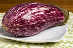 colorful striped eggplant on white plate - stock photo