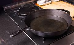 Cast iron skillet or fry pan on stove Stock Photos